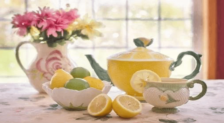 teacup set, vase with flowers, and bowl of lemons and limes