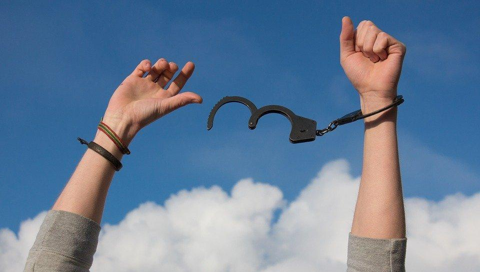 woman breaking free from handcuffs as metaphor for addiction recovery