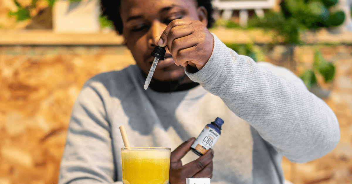 UK man dropping cbd oil extract into orange juice