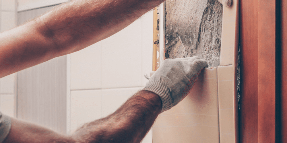 handyman uncovering absestos in house wall