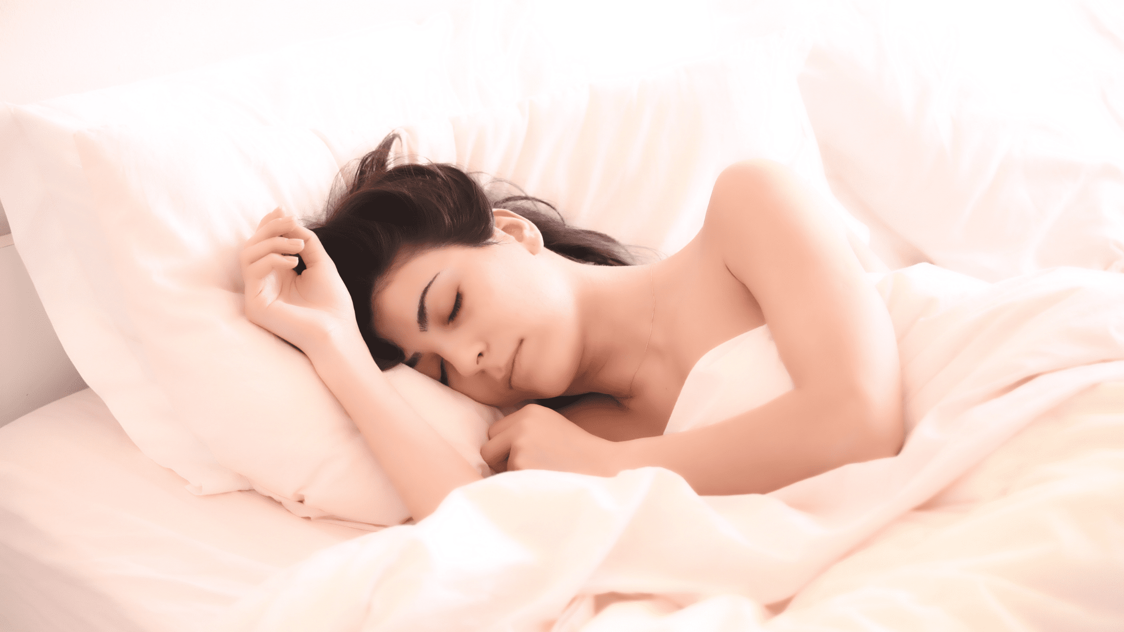 young woman sleeping in bed with pink sheets after using cannabis