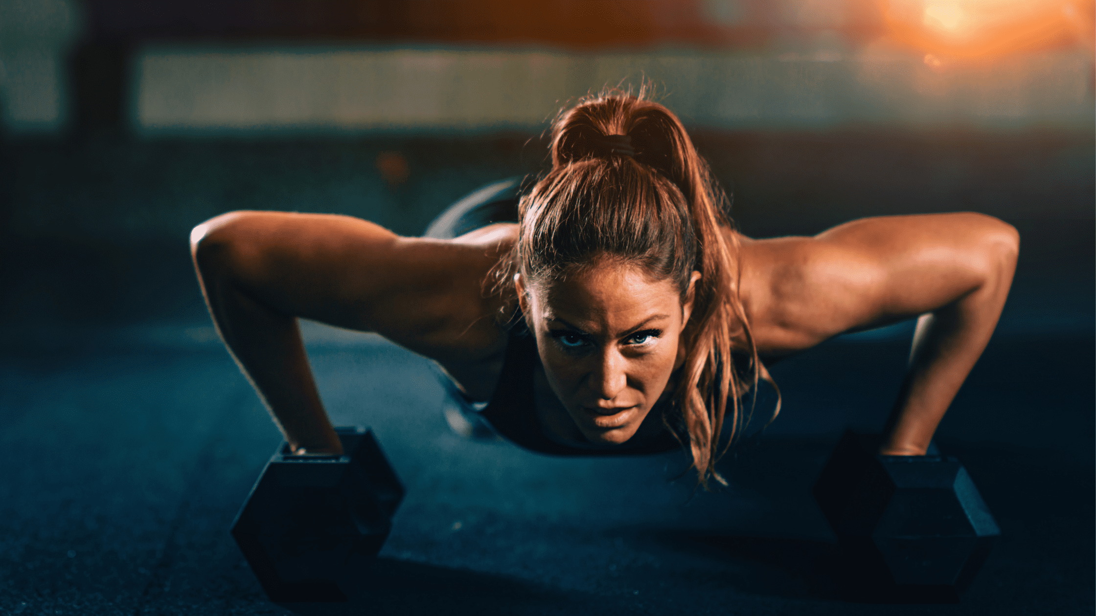 young woman doing pushups on weights after smoking cannabis
