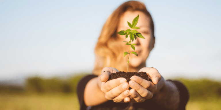 woman holding a baby cannabis plant in her