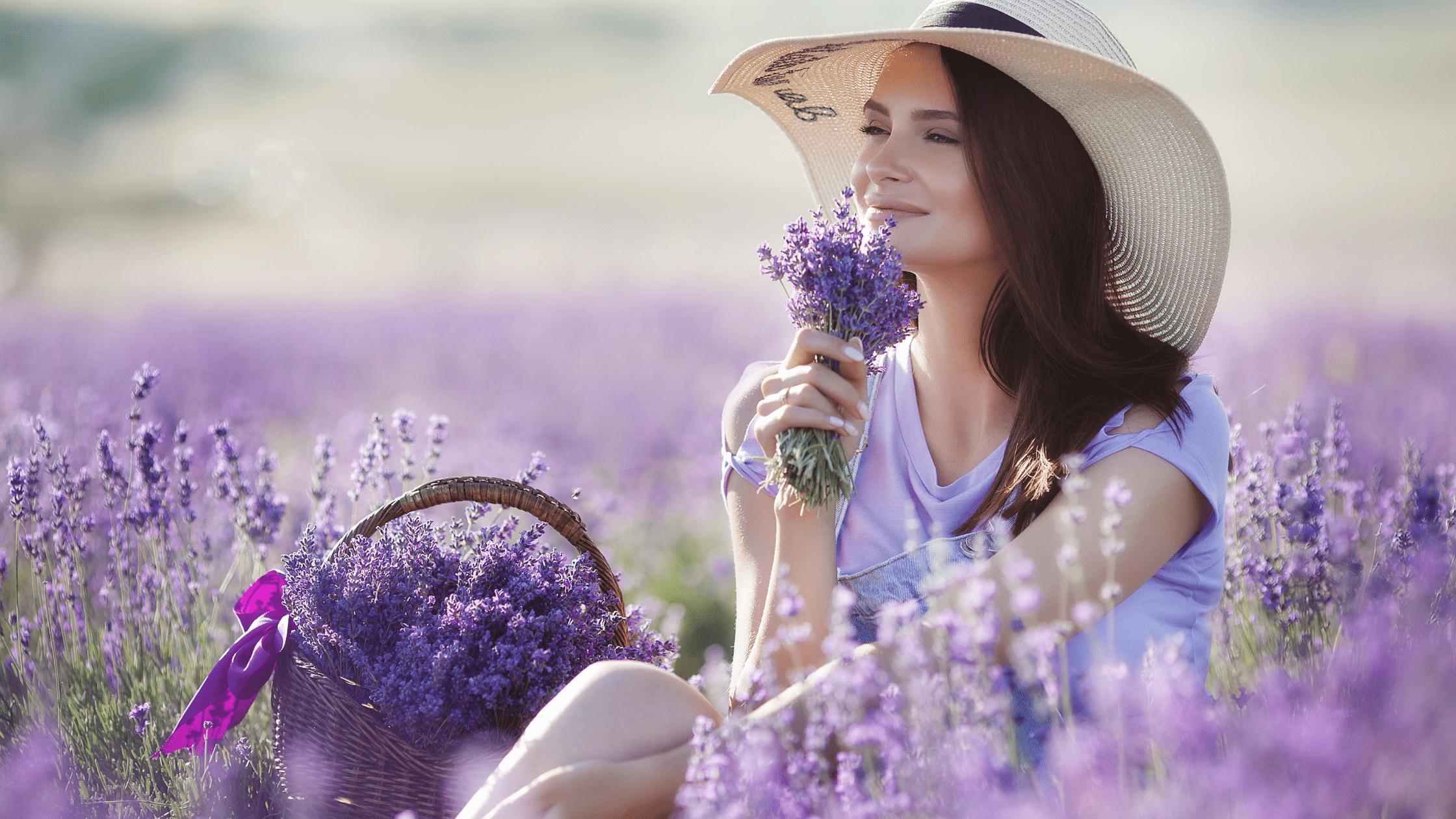 woman with hat on in in lavender field smelling the terpenes in the flowers